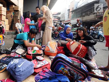 Warga memilih tas yang dijajakan pedagang kaki lima di sekitar Pasar Asemka, Jakarta, Rabu (5/7). Jelang bergantinya tahun ajaran baru, sejumlah warga berburu peralatan sekolah di kawasan Pasar Asemka Jakarta. (Liputan6.com/Helmi Fithriansyah)