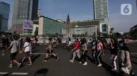 Warga berolahraga di area Car Free Day (CFD) kawasan MH Thamrin, Jakarta, Minggu (21/6/2020). Kegiatan hari bebas kendaraan bermotor atau CFD Jakarta kembali dibuka pada Minggu (21/6) ini diiringi dengan sejumlah protokol kesehatan. (Liputan6.com/Johan Tallo)