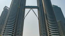 Sejumlah orang memotret di depan Menara Kembar Petronas, Kuala Lumpur, Malaysia, 18 Maret 2016. Kombinasi antara gedung pencakar langit dan situs bersejarah serta perpaduan harmonis beragam budaya semakin memperkaya pesona khas dari Kuala Lumpur. (Xinhua/Chong Voon Chung)