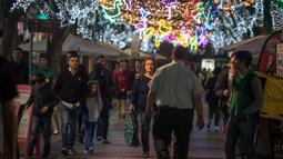 Orang-orang berjalan di bawah lampu Natal yang menghiasi jalan Santa Cruz de Tenerife di pulau Canary Tenerife, Spanyol (19/12). (AFP Photo/Desiree Martin)