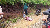 Seorang ibu melahirkan di tengah jalan yang dikeliling hutan di Kawasan Lebak Banten. Hal ini lantaran infrastruktur yang buruk. (Liputan6.com/Yandh Deslatama)