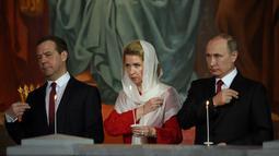 Presiden Rusia Vladimir Putin (kanan) bersama Perdana Menteri Rusia Dmitry Medvedev (kiri) dan istrinya Svetlana saat menjalani prosesi Paskah Ortodoks di Gereja Katedral Kristus Juru Selamat di Moskow, Rusia,(16/4). (AFP Photo / Vasily Maximov)