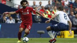 Gelandang Liverpool, Mohamed Salah, berusaha melewati gelandang Tottenham Hotspur, Harry Winks, pada laga Premier League di Stadion Wembley, Sabtu (15/9/2018). Tottenham Hotspur takluk 1-2 dari Liverpool. (AFP/Ian Kington)