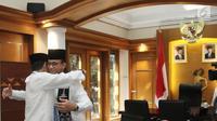 Wakil Gubernur DKI Jakarta Sandiaga Uno memeluk Gubernur Anies Baswedan saat menyampaikan surat pengunduran diri di Balai Kota, Jumat (10/8). Keduanya berpelukan mengingat harus berpisah menjadi rekan kerja memimpin Ibu Kota (Liputan6.com/Herman Zakharia)
