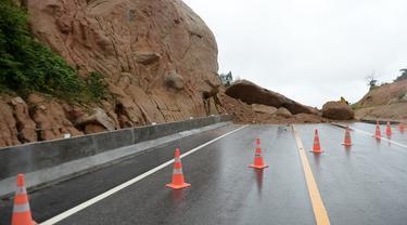 Batu-batu besar menutupi jalan raya ke bandara Narathiwat menyusul tanah longsor setelah hujan lebat di Thailand selatan (25/11/2019). Wilayah selatan Thailand akan memasuki musim hujan lebat tiga bulan dari November hingga Januari. (AFP/Madaree Tohlala)