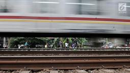 Kereta melintas saat anak-anak bermain di rel kereta api kawasan Jakarta Timur, Kamis (3/1). Minimnya lahan terbuka hijau memaksa anak-anak setempat memilih kawasan rel kereta api sebagai lokasi bermain. (Merdeka.com/Iqbal Nugroho)