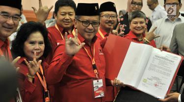 Sekjen PDIP Hasto Kristiyanto (tengah) menunjukkan daftar bakal caleg ke KPU di Jakarta, Selasa (17/7). Hasto tampak beberapa kali mengacungkan salam metal. (Merdeka.com/Iqbal Nugroho)