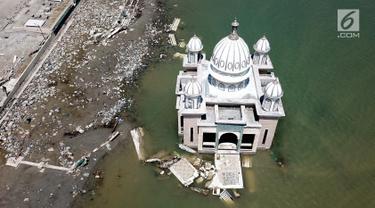 Pandangan udara Masjid Terapung Arqam Bab Al Rahman pasca gempa dan tsunami Palu di Pantai Talise, Sulawesi Tengah. Bangunan masjid yang terletak di pinggir pantai terlihat utuh meski sebagian bangunannya tenggelam. (Liputan6.com/Fery Padolo)