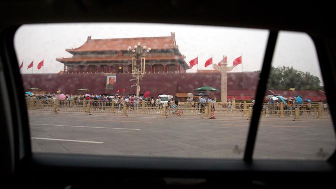 Foto mantan pemimpin Cina Mao Zedong terlihat melalui jendela mobil di Gerbang Tiananmen di sebelah Lapangan Tiananmen di Beijing (4/6/2019). Pemerintah China meningkatkan keamanan di sekitar Lapangan Tiananmen di pusat Beijing jelang peringatan tragedi Tiananmen 1989. (AP Photo/Mark Schiefelbein)