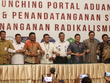 Menkominfo Johnny G. Plate (keempat kiri) bersama sebelas Kementerian dan lembaga negara  usai penandatangan kerja sama pembuatan portal aduan untuk aparatur sipil negara (ASN), Jakarta, Selasa (12/11/2019). Portal ini bisa melaporkan ASN yang diduga terpapar radikalisme (Liputan6.com/Faizal Fanani)