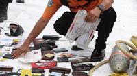 Petugas mengecek dan mengidentifikasi barang temuan yang diduga milik penumpang pesawat Lion Air JT 610 di Pelabuhan JICT 2, Jakarta, Selasa (30/10). Sebelumnya, pesawat Lion Air JT-610 jatuh diperairan Kerawang. (Liputan6.com/Helmi Fithriansyah)