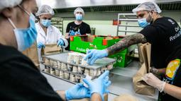 """Para sukarelawan menyiapkan paket makanan untuk orang-orang yang membutuhkan di Barcelona, Spanyol (25/6/2020). Spanyol telah memasuki tatanan """"Normal Baru"""" pada 21 Juni, dengan mengizinkan kembali warga untuk bebas bepergian di seluruh wilayah negara tersebut. (Xinhua/Balai Kota Barcelona)"""