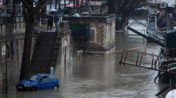 Sebuah mobil melintasi banjir di tepi sungai Seine, Paris (22/1). Sungai Seine telah berubah menjadi torrent berlumpur yang kuat yang telah menenggelamkan taman dan jalan. (AFP Photo/Stephane De Sakutin)