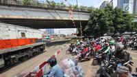 Pengendara menanti di pintu perlintasan kereta sebidang di Jalan KH Mas Mansyur, Jakarta, Senin (30/10). Perlintasan sebidang ini rencananya segera ditutup karena dianggap menjadi salah satu titik kemacetan di Jakarta Pusat. (Liputan6.com/Angga Yuniar)