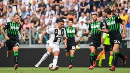Striker Juventus, Cristiano Ronaldo, berusaha melewati kepungan pemain Sassuolo pada laga Serie A di Stadion Juventus, Turin, Minggu (16/9/2018). CR 7 cetak dua gol, Juve menang 2-0 atas Sassuolo. (AFP/Miguel Medina)