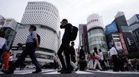 Orang-orang mengenakan masker mencegah penyebaran coronavirus baru berjalan di atas penyeberangan pejalan kaki di Tokyo, Senin, (20/7/2020). Ibukota Jepang hari Senin mengkonfirmasi lebih dari 160 kasus virus corona baru. (AP Photo/Eugene Hoshiko)