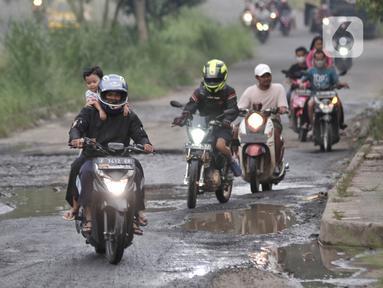 Pengendara motor melintasi jalan rusak dan berlubang di Jalan Tegar Beriman, Cibinong, Bogor, Minggu (31/5/2020). Sudah berbulan-bulan akses yang dikenal sebagai jalan Pemda Cibinong ini sangat memprihatinkan hingga sering menyebabkan kecelakaan terlebih saat musim hujan. (merdeka.com/Iqbal Nugroho)