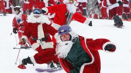 Pemain ski dan snowboarder berpakaian Santa Claus menuruni lereng gunung saat Santa Sunday ke-19 di Newry, Maine, AS, Minggu (2/12). Santa Sunday merupakan acara amal tahunan. (AP Photo/Robert F. Bukaty)