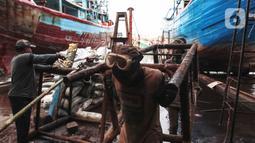 Buruh melakukan perbaikan kapal nelayan di Galangan kapal, Muara Angke, Jakarta, Minggu (23/12/2020). Bengkel kapal tersebut menjadi tumpuan pendapatan para pengusaha kapal barang dan ikan. (Liputan6.com/Angga Yuniar)