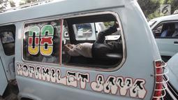 Seorang sopir angkot tidur di dalam mobilnya yang diparkir di depan Balai Kota DKI Jakarta, Rabu (31/1). Mereka menolak penutupan Jalan Jatibaru dan menuntut agar Pemprov DKI Jakarta segera membuka kembali jalan tersebut. (Liputan6.com/Arya Manggala)
