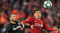 Gelandang Liverpool, Roberto Firmino, duel udara dengan bek Salzburg, Andreas Ulmer, pada laga Liga Champions di Stadion Anfield, Liverpool, Rabu (2/10). Liverpool menang 4-3 atas Salzburg. (AFP/Paul Ellis)