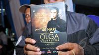 Warga menunjukkan kenang-kenangan buku Yassin seusai acara tahlilan 40 hari meninggalnya Olga Syhaputra di kediaman orang tua Olga di kawasan Duren Sawit, Jakarta, Rabu (6/5/2015). (Liputan6.com/Panji Diksana)