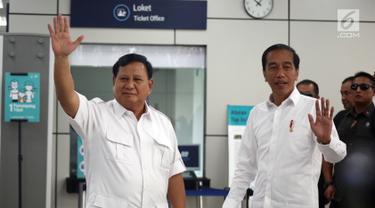 Presiden terpilih Joko Widodo atau Jokowi dan Ketua Umum Partai Gerindra Prabowo Subianto melambaikan tangan saat bertemu di Stasiun MRT Lebak Bulus, Jakarta, Sabtu (13/7/2019). Keduanya tampak akrab saat bertemu. (Liputan6.com/JohanTallo)