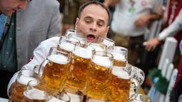 Oliver Struempfel membawa gelas bir sambil berjalan untuk memecahkan rekor pada festival tradisional Gillamoos di Abensberg, Jerman, Minggu (3/9). Ia berhasil menyusun 29 gelas dan membawanya dengan dua tangan dalam sekali jalan (Matthias Balk/dpa via AP)