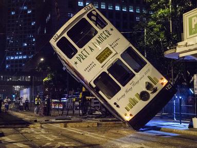 Sebuah trem double-decker diangkat menggunakan crane setelah terbalik di jalan utama di Hong Kong, Kamis (6/4). Kecelakaan yang terjadi tengah malam waktu setempat itu mengakibatkan 11 orang mengalami luka-luka. (ANTHONY WALLACE / AFP)