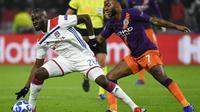 Pemain Lyon, Tanguy Ndombele berduel dengan Raheem Sterling pada laga lanjutan liga champions yang berlangsung di stadion Parc Olympique Lyonnais, Prancis, Rabu (28/11). Lyon bermain imbang 1-1 kontra Manchester City. (AFP/Jeff Pachoud)