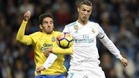 Cristiano Ronaldo (kanan) berebut bola dengan pemain Las Palmas, Pedro Bigas Rigo pada laga La Liga Santander di Santiago Bernabeu stadium, Madrid, (5/11/2017). Real Madrid menang 3-0. (AFP/Gabriel Bouys)