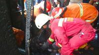 Petugas mengevakuasi jenazah bocah tewas terbakar dari lemari tempatnya bersembunyi. (Liputan6.com/Istimewa)
