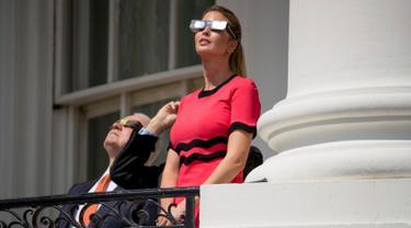 Putri Presiden AS Donald Trump, Ivanka Trump mengenakan kacamata khusus saat melihat gerhana matahari total dari balkon Gedung Putih, Senin (21/8). Gerhana matahari total di Amerika Serikat dapat disaksikan langsung di 14 negara bagian. (AP/Andrew Harnik)
