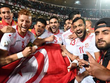 Pemain tim nasional sepak bola Tunisia melakukan selebrasi usai pertandingan melawan Libya di kualifikasi Piala Dunia 2018 di Stadion Olimpiade Rades, Tunisia (11/11). Tunisia berhasil lolos ke Piala Dunia 2018. (AFP Photo/Fethi Belaid)