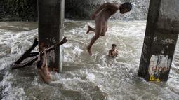 Sejumlah anak bermain di sungai dengan arus yang sangat deras akibat hujan lebat di bawah jembatan di Manila, Filipina (11/6). (AFP Photo/Noel Celis)