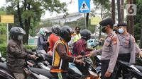 Petugas memberikan himbauan kepada pengendara untuk memutar balik di Pos Penyekatan Jalan Raya Bogor, Jakarta, Rabu (20/7/2021). Penyekatan tersebut merupakan tindak lanjut dari kebijakan Pemberlakuan Pembatasan Kegiatan Masyarakat (PPKM) Level 4 hingga 25 Juli 2021. (Liputan6.com/Herman Zakharia)
