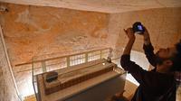Seorang pria mengambil gambar Mumi Raja Tutankhamun di makam bawah tanahnya (KV62) di Lembah Para Raja, Luxor, Mesir (31/1). Makam terkenal tersebut menjalani konservasi sembilan tahun oleh tim spesialis internasional. (AFP Photo/Mohamed El-Shahed)