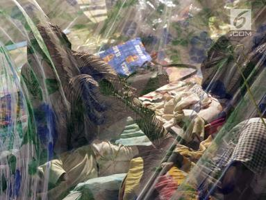Pencari suaka menidurkan anaknya di dalam tenda yang dibangun di atas trotoar depan kantor UNHCR Jalan Kebon Sirih, Jakarta, Jumat (5/7/2019). Para pencari suaka dari sejumlah negara berkonflik berharap UNHCR bisa segera memberikan jaminan perlindungan bagi mereka. (Liputan6.com/Helmi Fithriansyah)