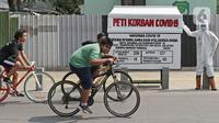 Pesepeda melintas di depan seni instalasi yang menggambarkan tenaga medis memegang peti jenazah korban COVID-19 di Kemang 1, Jakarta Selatan, Minggu (16/8/2020). Seni instalasi itu dipajang guna memberi peringatan kepada warga untuk tetap waspada terhadap COVID-19. (Liputan6.com/Herman Zakharia)