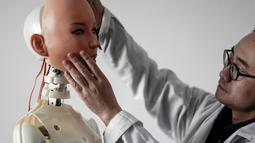 Seorang insinyur menempelkan wajah boneka seks ke kepala robot di sebuah laboratorium pabrik EXDOLL di Dalian, China, Kamis (1/2). EXDOLL menciptakan bonek seks pintar. (AFP PHOTO/FRED DUFOUR)
