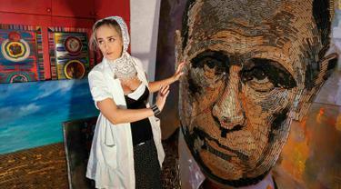 Seniman asal Ukraina, Dariya Marchenko memperlihatkan lukisan wajah Presiden Rusia, Vladimir Putin yang dibuatnya di Kiev, Ukraina (27/7/2015). 5.000 peluru dihabiskan Dariya yang diambil dari lokasi peperangan di Ukraina Timur. (REUTERS/Gleb Garanich)