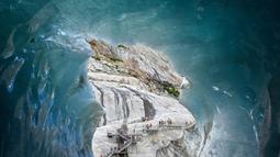 """Wisatawan mendaki tangga saat mengunjungi sebuah gua es, """"La Grotte de Glace"""", di gletser Mer de Glace (Lautan Es) di Chamonix-Mont-Blanc, Pegunungan Alpen Prancis, Jumat (19/7/2019). Gua yang berada di lereng Mont Blanc ini memiliki panjang 7 km dengan kedalaman 200 meter. (PHILIPPE DESMAZES/AFP)"""