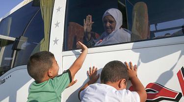 Calon jemaah haji asal Palestina melambaikan tangan kepada kerabatnya saat berangkat menuju Makkah di perbatasan Jalur Gaza dengan Mesir, Rafah, Kamis (25/7/2019). Suasana haru menghiasi momen pemberangkatan jemaah calon haji Palestina ke Tanah Suci. (SAID KHATIB/AFP)