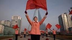 Kelompok Serikat Wanita Sosialis mengibarkan bendera saat melakukan propaganda di depan Hotel Ryugyong, Pyongyang, Korea Utara, Sabtu (9/3). Mereka melakukan aksinya di lokasi-lokasi strategis sekitar Pyongyang pada hari Senin-Sabtu. (Ed Jones/AFP)
