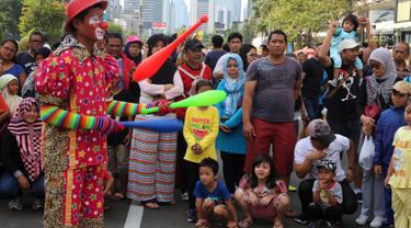 Komunitas dari Aku Badut Indonesia meramaikan kegiatan Car Free Day (CFD) di kawasan Thamrin, Jakarta, Minggu (6/1). Mereka melakukan atraksi akrobatik untuk menggalang dana bagi korban bencana tsunami Selat Sunda. (Liputan6.com/Johan Tallo)