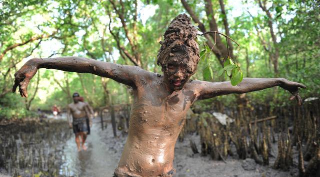 Seorang remaja berpose dengan badan penuh lumpur saat mengikuti Mebuug-buugan di desa Kedonganan, Bali (18/3). Mebuug-buugan ini diadakan sehari setelah Nyepi, bertujuan untuk menetralisir sifat-sifat buruk. (AFP/Sony Tumbelaka)