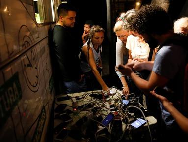 Warga nampak mengerubungi sebuah generator yang menjadi tempat pengisian baterai ponsel umum di Caracas, Venezuela (26/3). Akibat pemadaman listrik yang masih terjadi di Venezuela, warga harus mengantre dan berebut untuk mengisi daya baterai ponsel milik mereka. (Reuters/Carlos Garcia Rawlins)