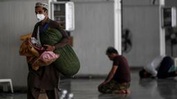 Seorang umat muslim dengan mengenakan masker membawa barang-barangnya saat tiba untuk beritikaf di Masjid Agung Faisal di Islamabad, Pakistan, Kamis (14/5/2020). Itikaf adalah berdiam diri di masjid untuk mendekatkan diri kepada Allah swt pada sepuluh hari terakhir bulan Ramadan (Aamir QURESHI /AFP)