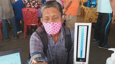 Seorang pedagang di Pasar Raya Padang sedang melakukan cek kesehatan d=sebelum divaksin. (Liputan6.com/ Novia Harlina)