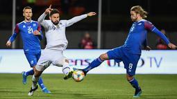 Penyerang timnas Prancis, Olivier Giroud berebut bola dengan gelandang Islandia Birkir Bjarnason dalam laga lanjutan Grup H Kualifikasi Piala Eropa 2020. di Stadion Laugardalsvollur, Reykjavik, Jumat (11/10/2019). Gol tunggal Giroud antarkan Prancis menang 1-0 atas Islandia (Jonathan NACKSTRAND/AFP)
